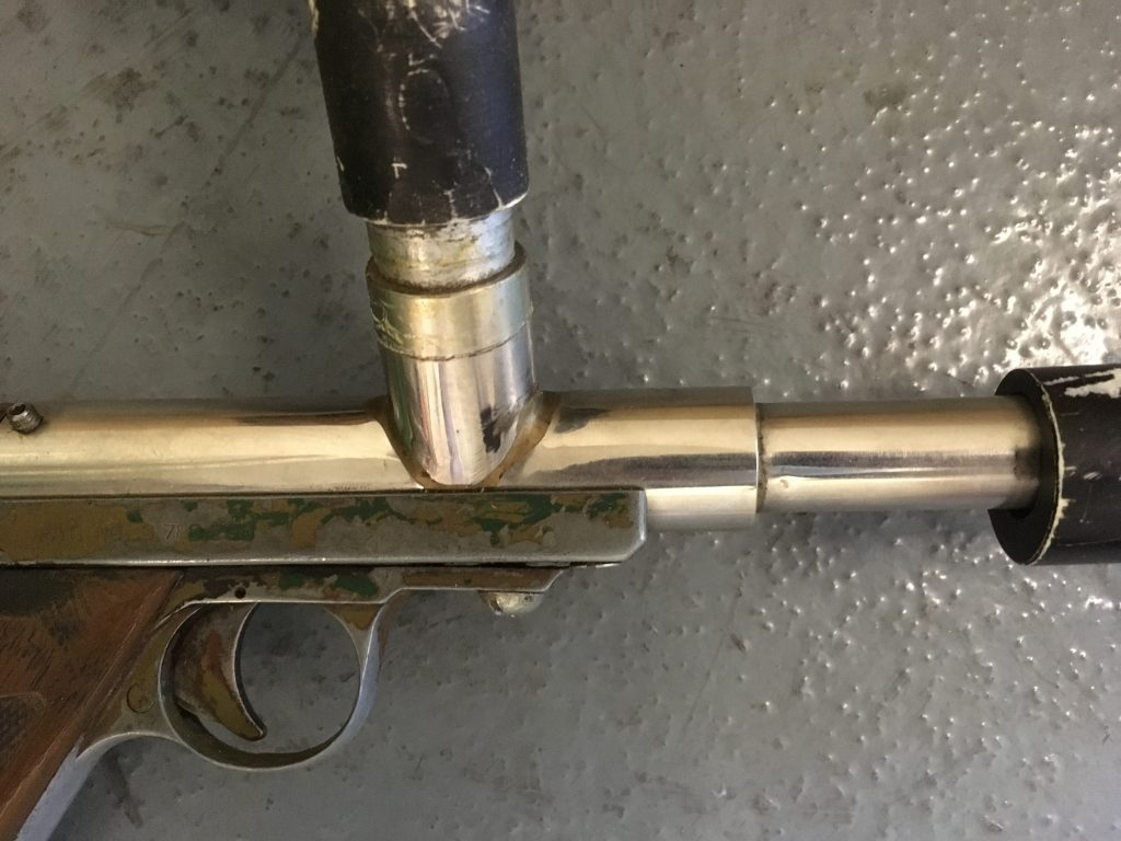 Close up of right side showing feedneck attachment on stainless Nelspot pistol.